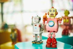 Vecchio giocattolo rosa d'annata del robot su un fondo confuso di colore Fotografia Stock
