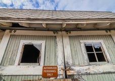 Vecchio granaio abbandonato rustico con il segno autorizzato del personale sulla porta con le finestre rotte Fotografie Stock