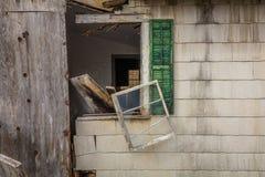 Vecchio granaio abbandonato rustico con il segno autorizzato del personale sulla porta con le finestre rotte Fotografia Stock