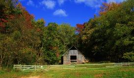 Vecchio granaio circondato dagli alberi di caduta e del cielo blu immagini stock