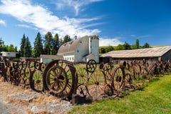 Vecchio granaio con il recinto fatto dalle vecchie ruote d'acciaio Fotografie Stock