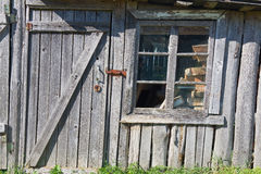 Vecchio granaio di legno con una finestra a porta chiusa e rotta Fotografia Stock Libera da Diritti