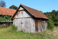Vecchio granaio di legno dilapidato abbandonato inutilizzato con l'entrata imbarcata ed i bordi incrinati circondati con gli albe immagine stock libera da diritti