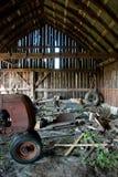 Vecchio granaio di legno in pieno di roba di rifiuto e del trattore d'arrugginimento Immagini Stock Libere da Diritti