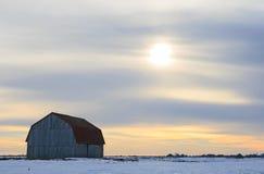 Vecchio granaio di legno in un campo nevoso Fotografie Stock Libere da Diritti