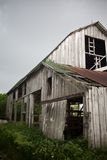 Vecchio, granaio esposto all'aria con il tetto arrugginito frustato da Wind Immagini Stock