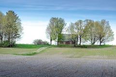 Vecchio granaio nel Michigan rurale con il modo dell'azionamento lungo ed il campo arato fresco Fotografia Stock