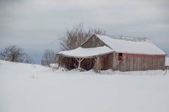 Vecchio granaio rosso stagionato nell'inverno Fotografie Stock Libere da Diritti