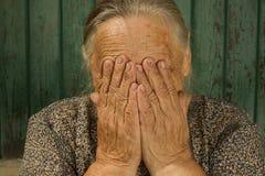 Vecchio gridare della nonna, coprente il suo fronte di mani, ritratto Fotografia Stock