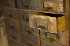 Vecchio guardaroba di legno con i piccoli cassetti per la conservazione delle lettere, mini-guardaroba fatto a mano del XIX secol immagine stock
