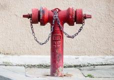 Vecchio idrante antincendio metallico rosso sulla via Fotografia Stock