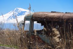 Vecchio il bus russo sovietico abbandonato ed arrugginito in mezzo alle canne ed all'agricoltura sistema con il Mt L'Ararat sui p Fotografia Stock