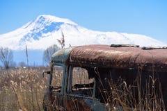 Vecchio il bus russo sovietico abbandonato ed arrugginito in mezzo alle canne ed all'agricoltura sistema con il Mt L'Ararat sui p Immagine Stock