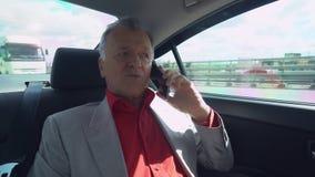 Vecchio - il capo invecchiato ha conversazione telefonica con il socio commerciale sul modo lavorare stock footage
