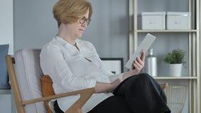 Vecchio Internet senior di lettura rapida della donna sul PC della compressa, sedentesi sullo strato archivi video