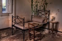 Vecchio letto arrugginito in casa rovinoso Immagini Stock