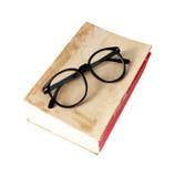 Vecchio libro con i vetri su bianco Fotografia Stock