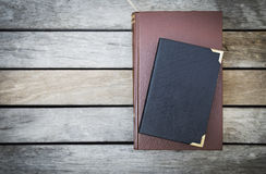 Vecchio libro con la copertura di cuoio sul fondo di legno d'annata del pavimento Fotografia Stock