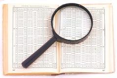 Vecchio libro e numeri sotto la lente di ingrandimento Immagine Stock