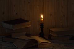 Vecchio libro e una candela Immagini Stock