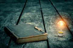 Vecchio libro stracciato su una tavola di legno Leggendo dal lume di candela Composizione d'annata Libreria antica Immagine Stock