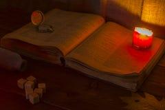 Vecchio libro sulla tabella La bibbia santa aperta è sulla tavola Orologio da tasca d'annata Una candela bruciante sopra la bibbi Immagini Stock Libere da Diritti
