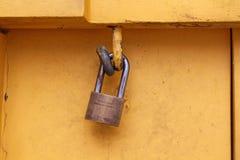 Vecchio lucchetto arrugginito del primo piano che appende sulla parete di legno gialla Immagine Stock
