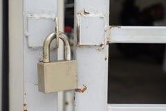 Vecchio lucchetto che appende sulla porta grigia del metallo Immagine Stock