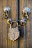 Vecchio lucchetto del metallo su una porta di legno immagine stock