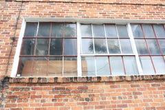 Vecchio magazzino del mattone della città con Windows d'annata immagini stock libere da diritti