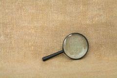 Vecchio magnifier nero sulla priorità bassa del drapery Fotografia Stock
