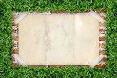 Vecchio manifesto nel telaio dell'erba Fotografia Stock Libera da Diritti