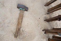 Vecchio martello con una maniglia di legno sul fondo della spiaggia di sabbia immagine stock