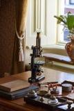 Vecchio microscopio sullo scrittorio del medico immagine stock libera da diritti