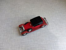 vecchio modello rosso dell'automobile su un fondo grigio Immagini Stock Libere da Diritti