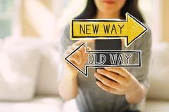 Vecchio modo o nuovo modo con la donna che per mezzo di uno smartphone immagine stock
