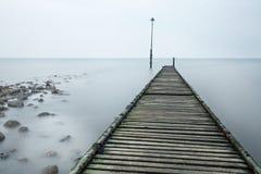 Vecchio molo decomposto con le rocce e la foschia del mare immagini stock