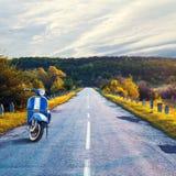 Vecchio motorino blu d'annata sui precedenti della strada che retrocede nella distanza Bello paesaggio Cielo nuvoloso immagine stock