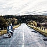 Vecchio motorino blu d'annata sui precedenti della strada che retrocede nella distanza Bello paesaggio modificato Viaggio c del c fotografia stock