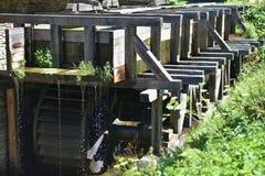 Vecchio mulino a acqua di legno nell'erba Immagini Stock Libere da Diritti