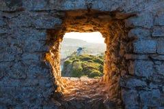 Vecchio mulino a vento attraverso la finestra in parete della fortezza Immagine Stock