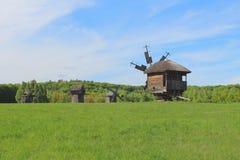 Vecchio mulino a vento di legno sul prato verde Immagini Stock Libere da Diritti