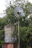 Vecchio mulino a vento funzionante con la cisterna Immagine Stock