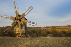 Vecchio mulino a vento in un campo vicino alla foresta al tramonto Fotografie Stock
