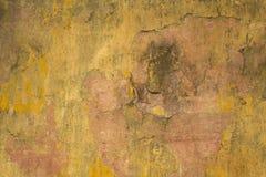 Vecchio muro di cemento rosa nocivo sporco con le crepe e la pittura misera gialla Struttura della superficie ruvida immagine stock libera da diritti