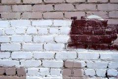 Vecchio muro di mattoni con le macchie bianche e rosse della pittura immagini stock libere da diritti
