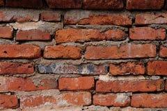 Vecchio muro di mattoni disordinato incollato da cemento Immagine Stock