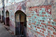 Vecchio muro di mattoni grungy con la porta incurvata fotografia stock