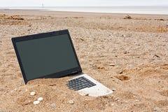 Computer portatile con computer personale sulla spiaggia Fotografia Stock