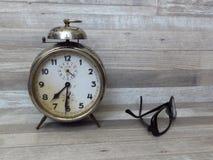 Vecchio orologio classico, tempo, allarme, annata, sveglia, occhiali, vetri, gente anziana, problemi di visione di vista Fotografie Stock Libere da Diritti